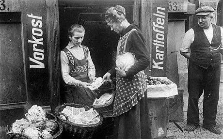 Pre War Germany was in financial crises which ultimately helped to sweep Hitler into power. Here, a woman purchases some food with a basket full of money. Germany's inflation rate was so high that they were printing 100 billion Deutchmark bills (i.e., a single $100,000,000,000 bill) for public use.
